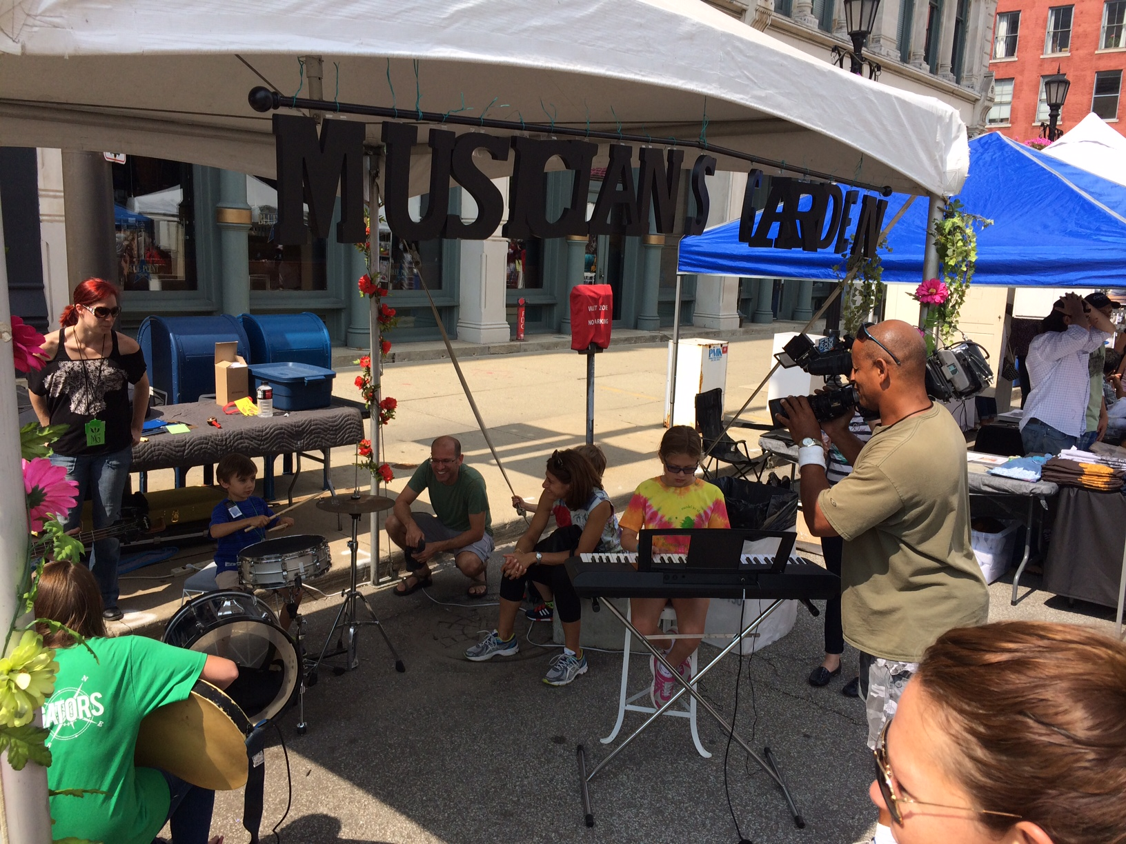 The Musicians Garden Booth was full of people of all ages playing music. Here a group of young kids makes music together for the first time as the local news cameraman captures the action.